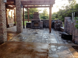 Pergola and stone patio with fireplace